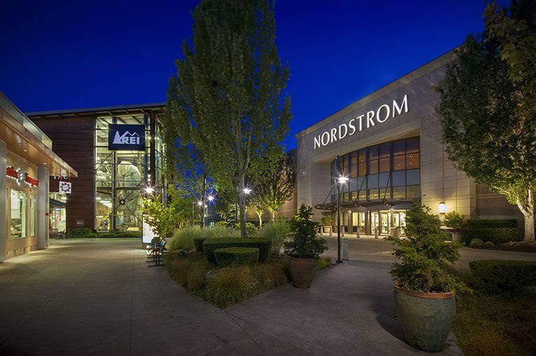 Outside Alderwood, the Nordstrom and REI storefronts are lit up at night with plants and lamps welcoming visitors.